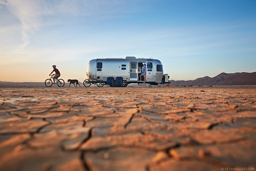 A family enjoys recreation with their Airstream trailer and bicycles in the arid, desert landscape near Joshua Tree National Park, California.